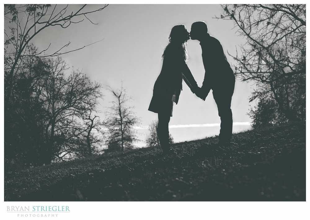 Shooting Winter Engagement Photos silhouette on hill