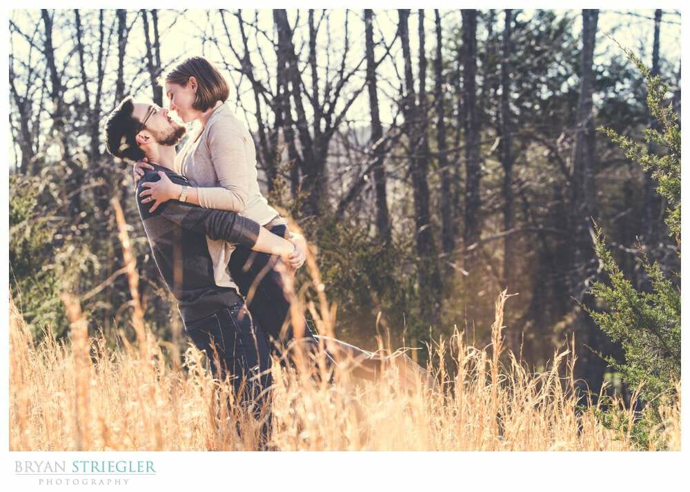 engagement photos in a field while picking her up