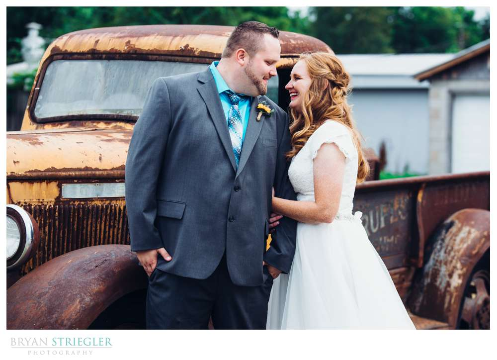 bride and groom in front of old truck