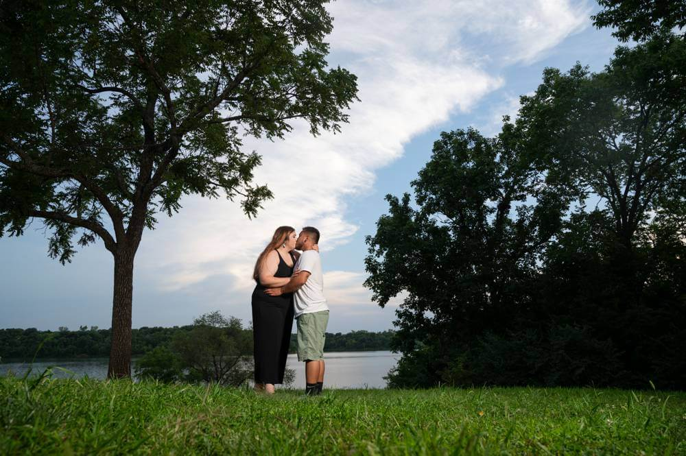 bright blue skies behind couple at Shawnee Mission Park during engagement session