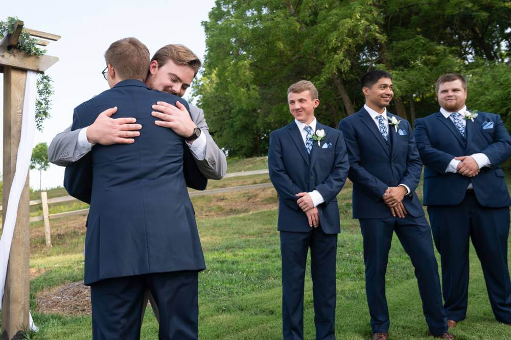bestman and brother hugging groom at wedding ceremony