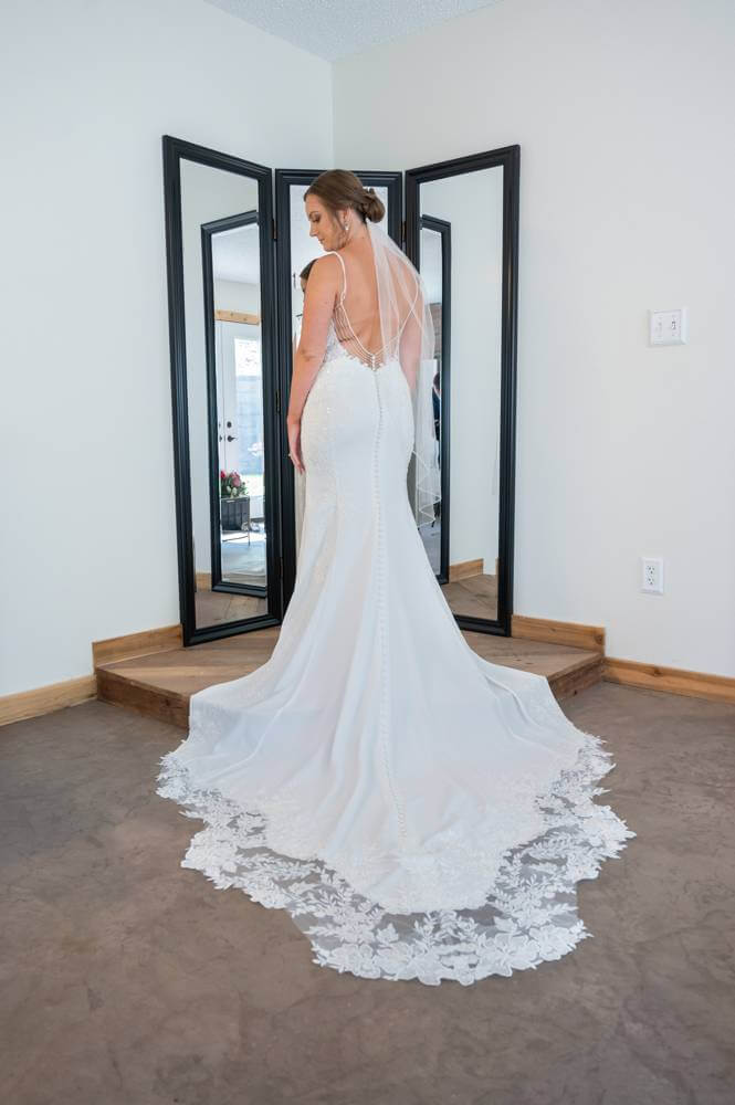 bride in wedding dress in front of mirror